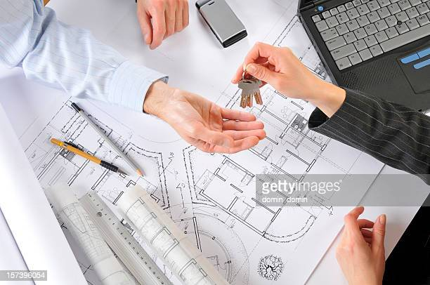 Developer giving new house keys to the client, building plans