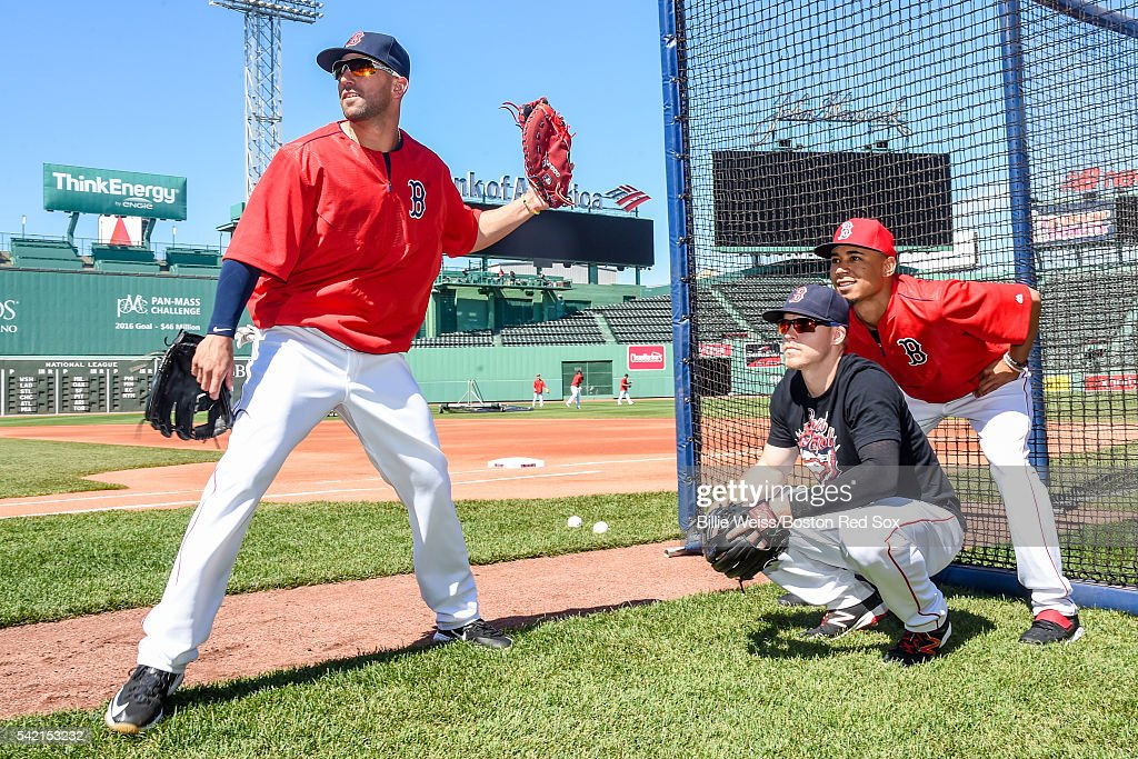 Deven Marrero #16, Brock Holt #12 and Mookie Betts #50 of the Boston Red Sox pretend to call balls and strikes during batting practice before a game against the Chicago White Sox on June 22, 2016 at Fenway Park in Boston, Massachusetts.