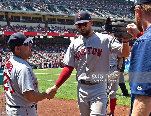 Deven Marrero of the Boston Red Sox gets a hand shake from Ruben Amaro Jr first base coach after a play in the sixth inning at Angel Stadium of...