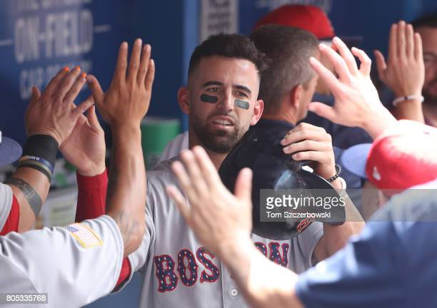 Deven Marrero of the Boston Red Sox is congratulated by teammates in the dugout after scoring a run in the second inning during MLB game action...