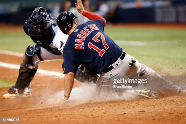 Deven Marrero of the Boston Red Sox slides home ahead of catcher Jesus Sucre of the Tampa Bay Rays off of an RBI single by Xander Bogaerts during the...