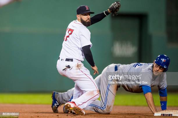 Deven Marrero of the Boston Red Sox tags out Luke Maile of the Toronto Blue Jays as he is picked off at second base during the fifth inning of a game...