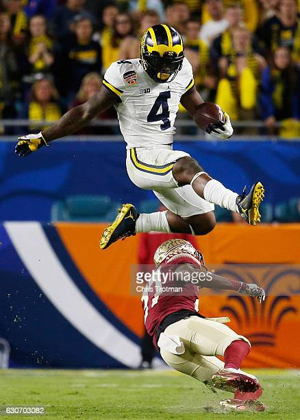 De'Veon Smith of the Michigan Wolverines leaps over Marquez White of the Florida State Seminoles in the third quarter during the Capitol One Orange...