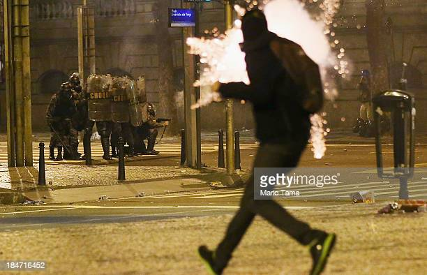 A device explodes as a demonstrator runs past police during clashes following a largely peaceful protest by teachers and supporters calling for...