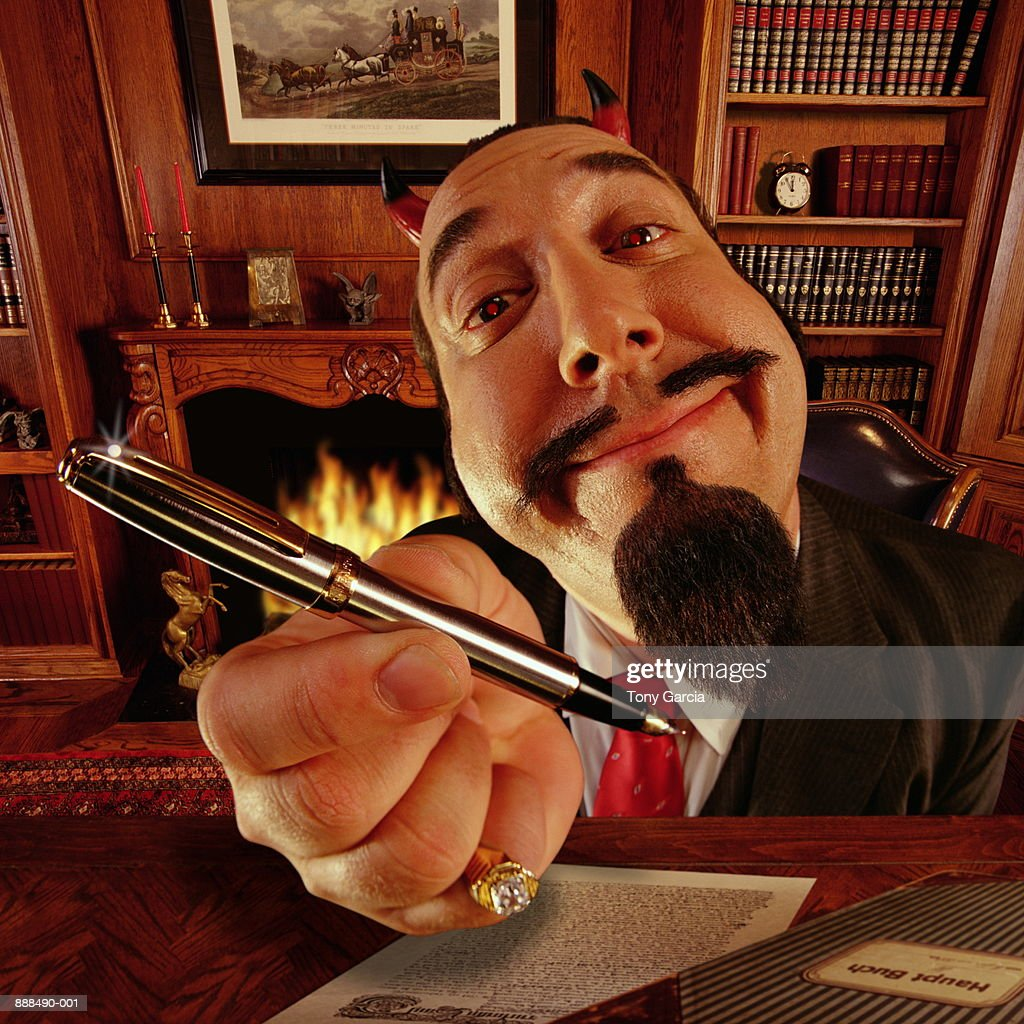Devil sitting at desk, holding pen (Digital Enhancement) : Stock Photo