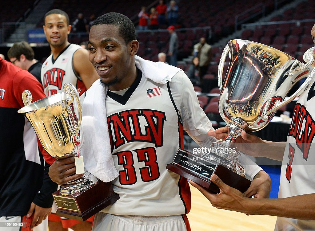 Deville Smith #33 of the UNLV Rebels holds the tournament's MVP trophy and the championship trophy after UNLV defeated the Mississippi State Bulldogs 82-66 to win the 2013 Continental Tire Las Vegas Classic at the Orleans Arena on December 23, 2013 in Las Vegas, Nevada.