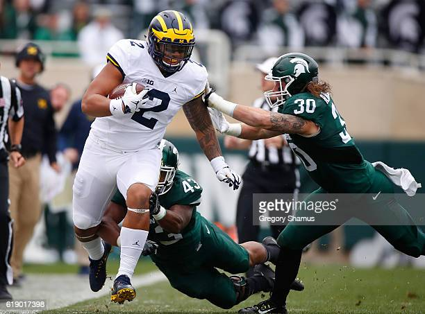 Devin Asiasi of the Michigan Wolverines tries to outrun the tackles of Riley Bullough and Ed Davis of the Michigan State Spartans during a first...