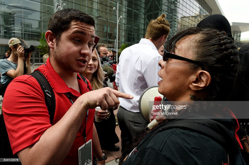 Devin Bilski, left, sticks his finger in the face of Anti-Trump protestor Brenda Carrasco during an Anti-Trump rally at the corner of 14th and California in Denver, Colorado on July 1, 2016.