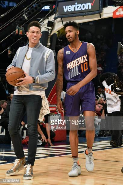 Devin Booker assists Derrick Jones Jr #10 of the Phoenix Suns dunks the ball during the Verizon Slam Dunk Contest on State Farm AllStar Saturday...