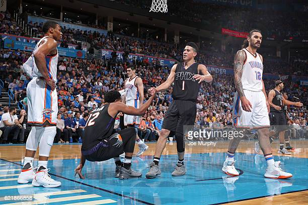 Devin Booker helps up TJ Warren of the Phoenix Suns before the gameb against the Oklahoma City Thunder on October 28 2016 at the Chesapeake Energy...