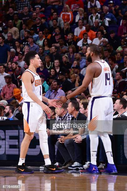 Devin Booker of the Phoenix Suns and Greg Monroe of the Phoenix Suns high five during the game against the Milwaukee Bucks on November 22 2017 at...