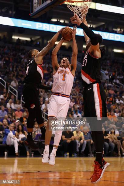 Devin Booker of the Phoenix Suns attempts a shot against Damian Lillard and Jusuf Nurkic of the Portland Trail Blazers during the first half of the...