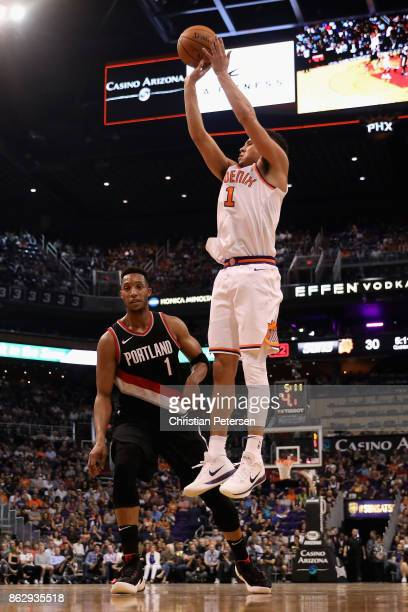 Devin Booker of the Phoenix Suns attempts a shot over Evan Turner during the first half of the NBA game at Talking Stick Resort Arena on October 18...