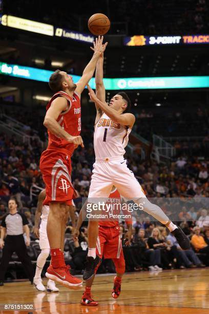 Devin Booker of the Phoenix Suns attempts a shot over Ryan Anderson of the Houston Rockets during the second half of the NBA game at Talking Stick...