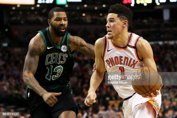 Devin Booker of the Phoenix Suns drives against Marcus Morris of the Boston Celtics during the second half at TD Garden on December 2 2017 in Boston...