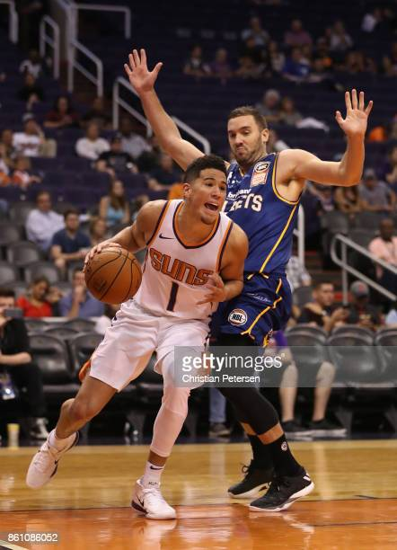 Devin Booker of the Phoenix Suns drives the ball past Adam Gibson of the Brisbane Bullets during the second half of the NBA preseason game at Talking...