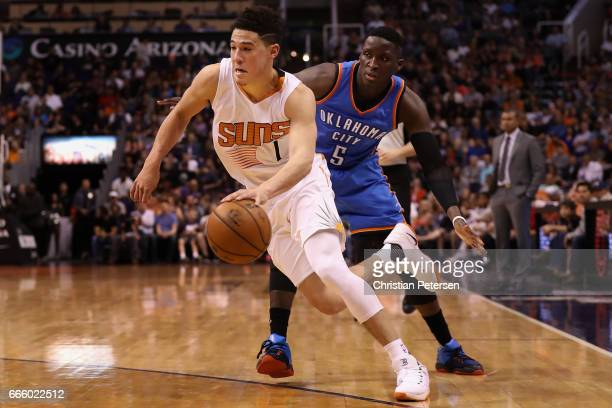 Devin Booker of the Phoenix Suns drives the ball past Victor Oladipo of the Oklahoma City Thunder during the second half of the NBA game at Talking...