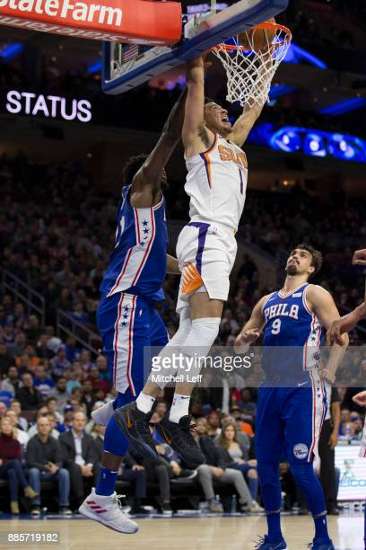 Devin Booker of the Phoenix Suns dunks the ball past Joel Embiid of the Philadelphia 76ers in the second quarter at the Wells Fargo Center on...