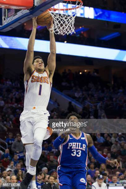 Devin Booker of the Phoenix Suns dunks the ball past Robert Covington of the Philadelphia 76ers in the first quarter at the Wells Fargo Center on...