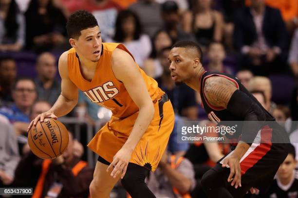 Devin Booker of the Phoenix Suns handles the ball against Damian Lillard of the Portland Trail Blazers during the NBA game at Talking Stick Resort...