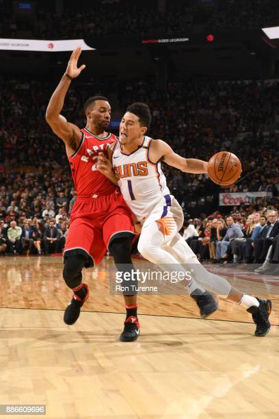 Devin Booker of the Phoenix Suns handles the ball against Norman Powell of the Toronto Raptors on December 5 2017 at the Air Canada Centre in Toronto...