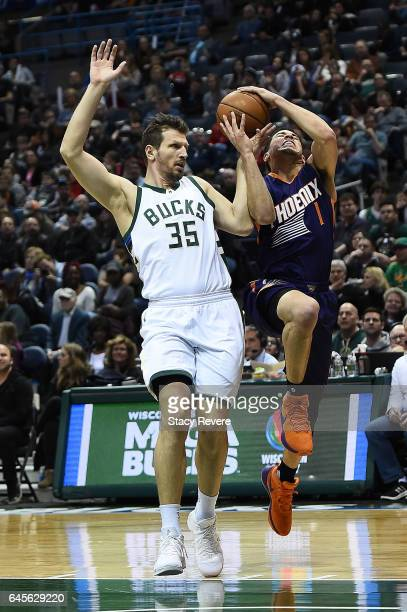 Devin Booker of the Phoenix Suns is fouled by Mirza Teletovic of the Milwaukee Bucks during the first half of a game at the BMO Harris Bradley Center...
