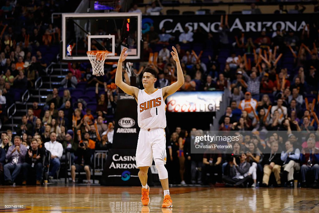 Devin Booker of the Phoenix Suns reacts after the Suns scored against the Charlotte Hornets during the second half of the NBA game at Talking Stick...