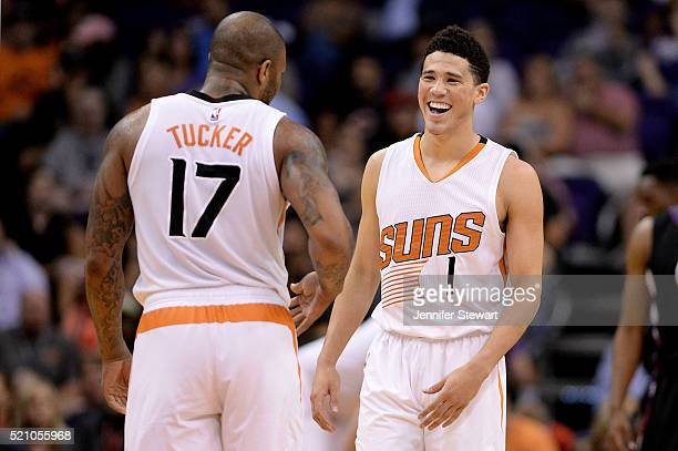 Devin Booker of the Phoenix Suns smiles in front of teammate PJ Tucker in the first half of the NBA game against the Los Angeles Clippers at Talking...