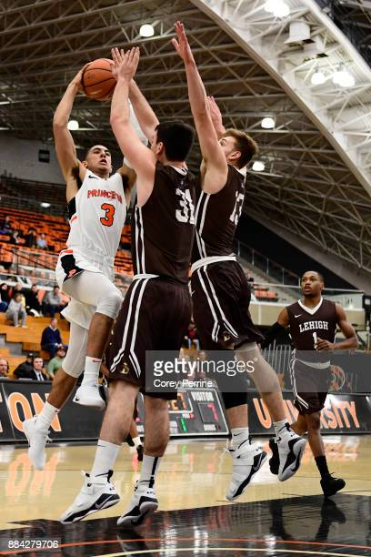 Devin Cannady of the Princeton Tigers drives to the basket Pat Andree and James Karnik defend and Kahron Ross of the Lehigh Mountain Hawks looks on...