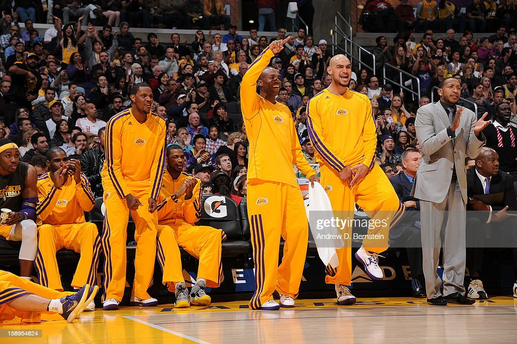 Devin Ebanks #3, Jodie Meeks #20, and Robert Sacre #50 of the Los Angeles Lakers celebrate from the bench during the game against the Philadelphia 76ers at Staples Center on January 1, 2013 in Los Angeles, California.