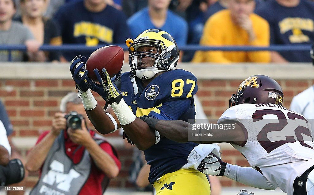 Devin Funchess #87 of the Michigan Wolverines makes the catch for a 46 yard gain over Jeremy Baltzar #22 of the Minnesota Golden Gophers during the fourth quarter of the game at Michigan Stadium on October 5, 2013 in Ann Arbor, Michigan. Michigan defeated Minnesota 42-13.