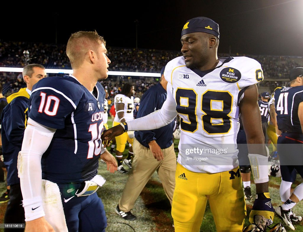 Devin Gardner #98 of the Michigan Wolverines chats with Chandler Whitmer #10 of the Connecticut Huskies after their contest at Rentschler Field on September 21, 2013 in East Hartford, Connecticut.
