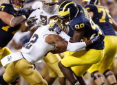 Devin Gardner of the Michigan Wolverines is greeted by Elijah Shumate of the Notre Dame Fighting Irish at Michigan Stadium on September 7 2013 in Ann...