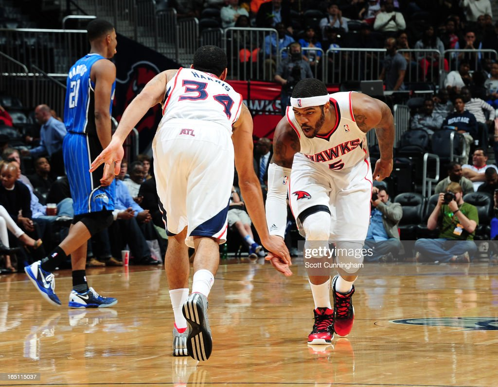 Devin Harris #34 and Josh Smith #5 of the Atlanta Hawks get excited against the Orlando Magic on March 30, 2013 at Philips Arena in Atlanta, Georgia.