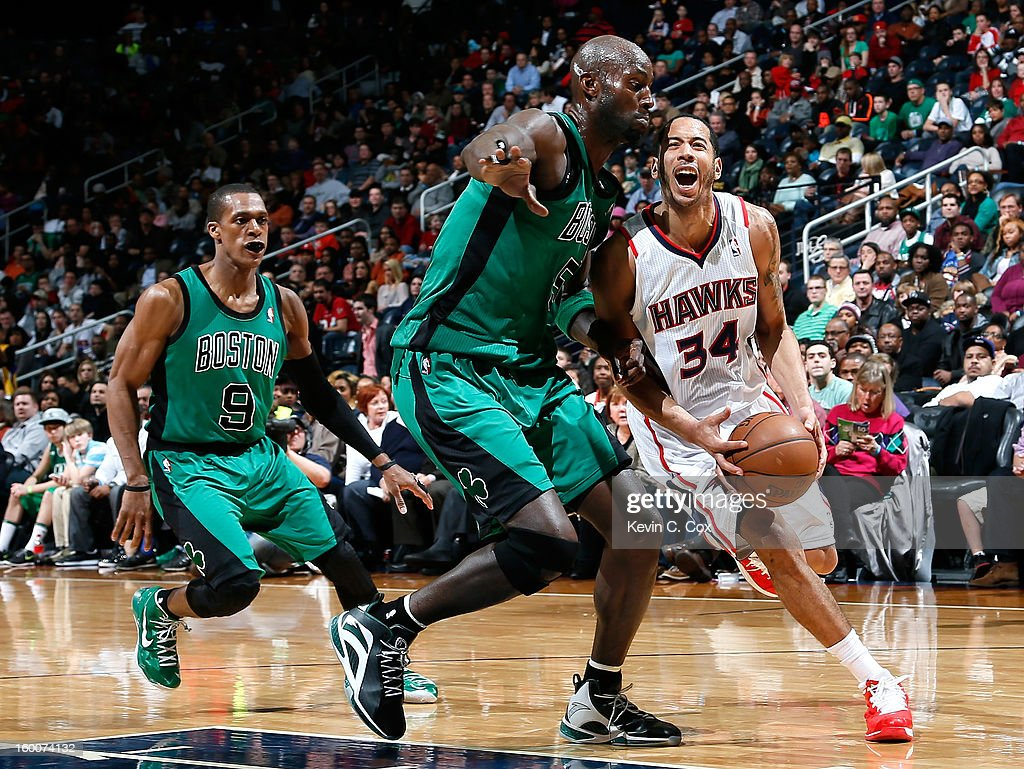 Devin Harris #34 of the Atlanta Hawks draws a foul as he drives past Rajon Rondo #9 and Kevin Garnett #5 of the Boston Celtics at Philips Arena on January 25, 2013 in Atlanta, Georgia.