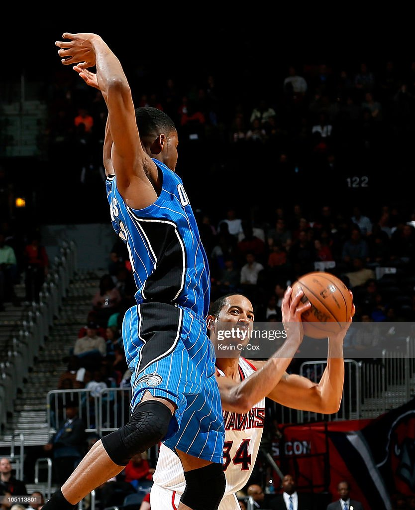 Devin Harris #34 of the Atlanta Hawks draws a foul from Maurice Harkless #21 of the Orlando Magic at Philips Arena on March 30, 2013 in Atlanta, Georgia.