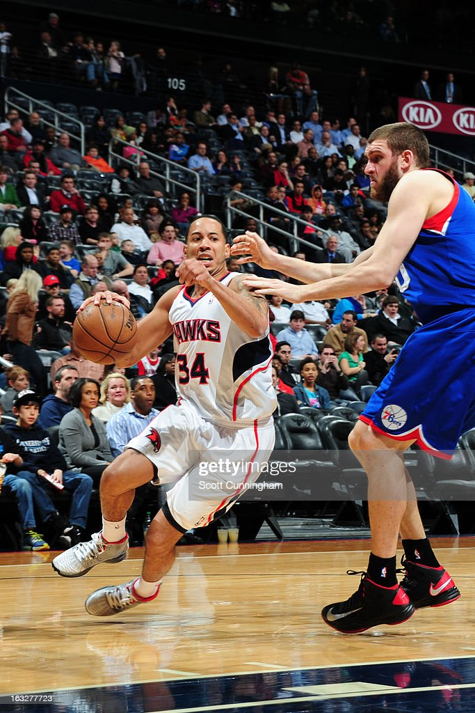 Devin Harris #34 of the Atlanta Hawks drives against Spencer Hawes #00 of the Philadelphia 76ers on March 6, 2013 at Philips Arena in Atlanta, Georgia.