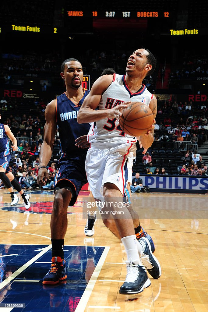 Devin Harris #34 of the Atlanta Hawks drives to the basket against Ramon Sessions #7 of the Charlotte Bobcats at Philips Arena on December 13 ,2012 in Atlanta, Georgia.