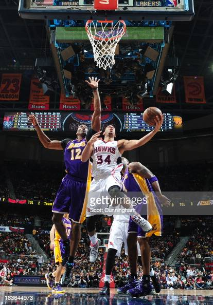 Devin Harris of the Atlanta Hawks goes up for the layup against Dwight Howard of the Los Angeles Lakers on March 13 2013 at Philips Arena in Atlanta...