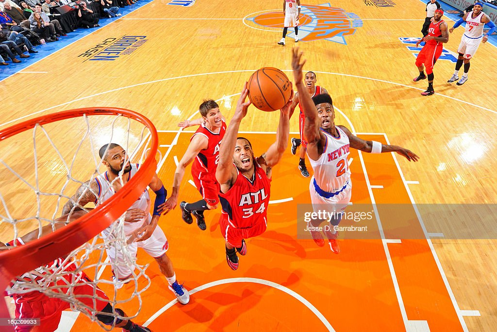 Devin Harris #34 of the Atlanta Hawks grabs a rebound against Iman Shumpert #21 of the New York Knicks at Madison Square Garden on January 27, 2013 in New York, New York.