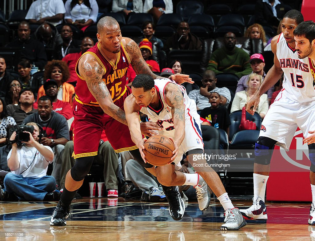 Devin Harris #34 of the Atlanta Hawks keeps control of the ball against Marreese Speights #15 of the Cleveland Cavaliers on April 1, 2013 at Philips Arena in Atlanta, Georgia.