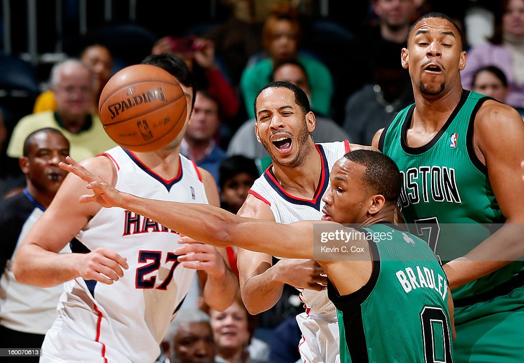 Devin Harris #34 of the Atlanta Hawks passes the ball backward as he drives into Avery Bradley #0 and Jared Sullinger #7 of the Boston Celtics at Philips Arena on January 25, 2013 in Atlanta, Georgia.