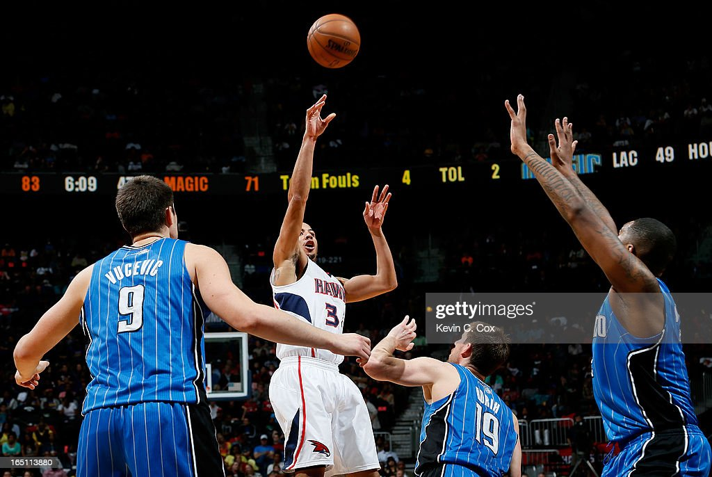 Devin Harris #34 of the Atlanta Hawks passes the ball over Nikola Vucevic #9, Beno Udrih #19, and Kyle O'Quinn #2 of the Orlando Magic at Philips Arena on March 30, 2013 in Atlanta, Georgia.