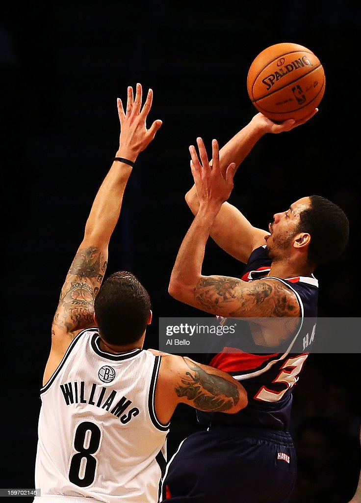 Devin Harris #34 of the Atlanta Hawks shoots over Deron Williams #8 of the Brooklyn Nets in the fourth quarter of the game at Barclays Center on January 18, 2013 in the Brooklyn borough of New York City.