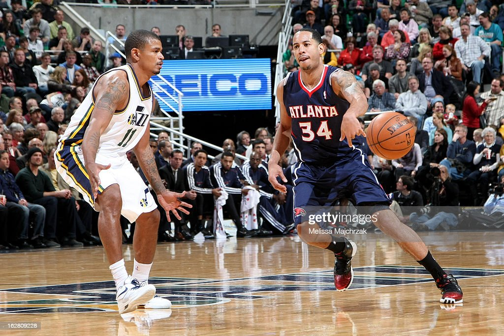 Devin Harris #24 of the Atlantic Hawks passes the ball away from Earl Watson #11 of the Utah Jazz at Energy Solutions Arena on February 27, 2013 in Salt Lake City, Utah.