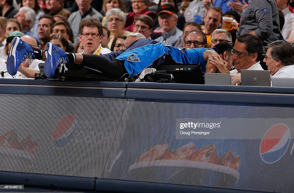 Devin Harris #20 of the Dallas Mavericks dives over the scorers table as he chases a loose ball against the Denver Nuggets at Pepsi Center on January 14, 2015 in Denver, Colorado.