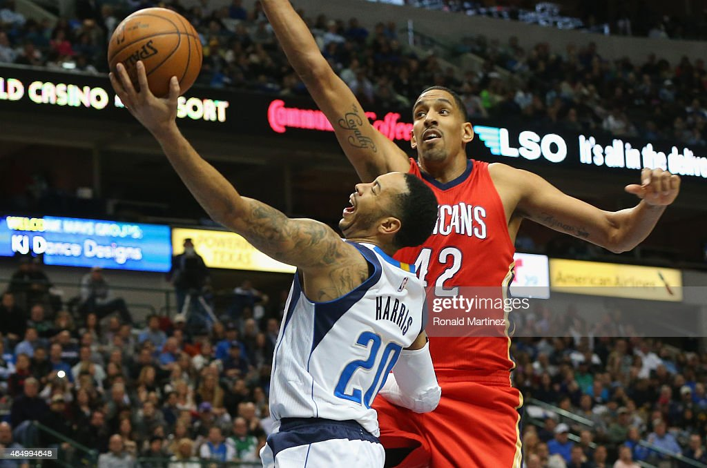 Devin Harris #20 of the Dallas Mavericks takes a shot against Alexis Ajinca #42 of the New Orleans Pelicans at American Airlines Center on March 2, 2015 in Dallas, Texas.