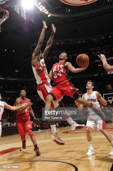 Devin Harris of the New Jersey Nets shoots against Amir Johnson of the Toronto Raptors during a game on December 17 2010 at the Air Canada Centre in...
