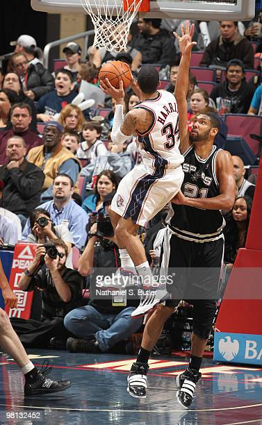 Devin Harris of the New Jersey Nets shoots against Tim Duncan of the San Antonio Spurs on March 29 2010 at the IZOD Center in East Rutherford New...