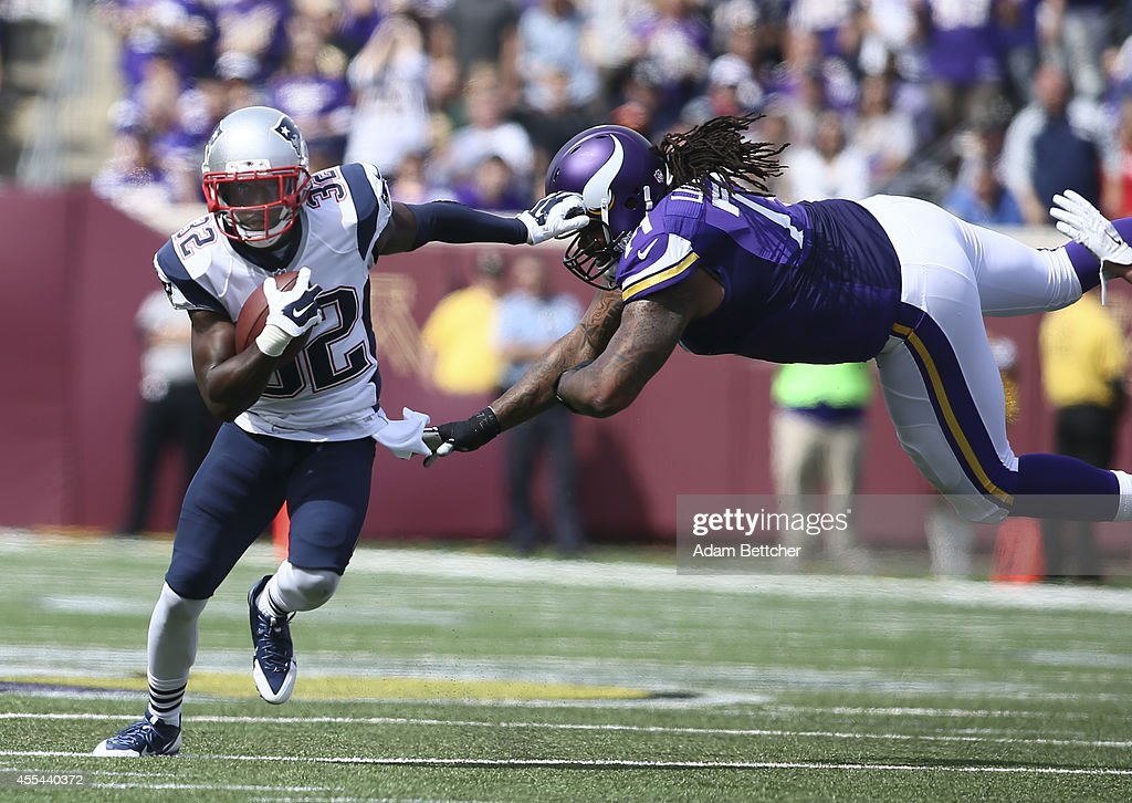 Devin McCourty of the New England Patriots avoids the block from Phil Loadholt of the Minnesota Vikings during an interception at TCF Bank Stadium on...